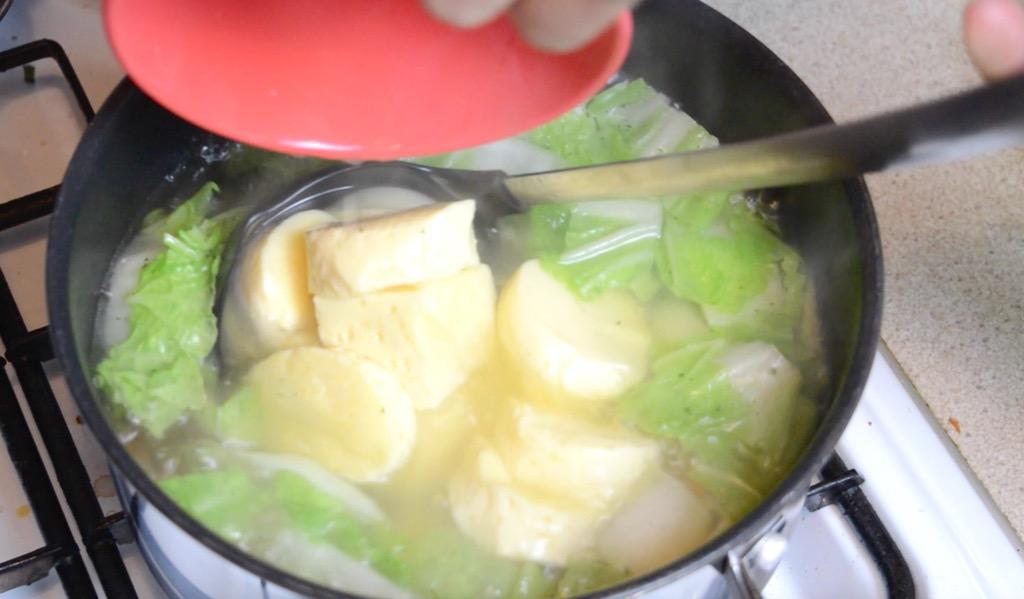 adding tofu to the soup