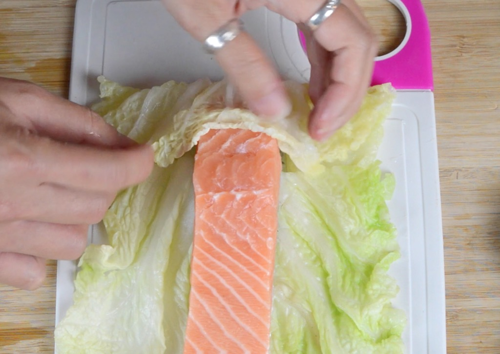 rolling the salmon in the cabbage leaf