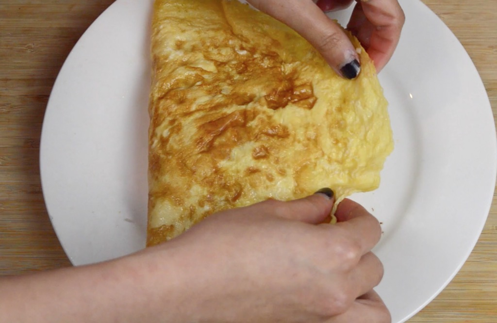 wrapping the fried rice in omelette